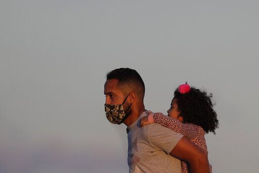 A child gets a piggy back ride from her father as the sun begins to set in Cruzeiro Square in Brasilia, Brazil, Friday, July 31, 2020. People gathered outdoors in the late afternoon as authorities eased the restrictions related to the new coronavirus, despite that Brazil's official COVID-19 death toll is the second highest in the world after the United States.