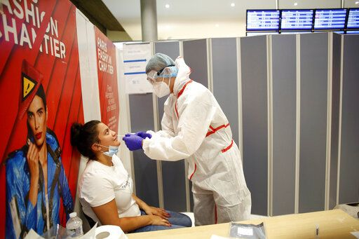 A health worker collects a nasal swab sample for COVID-19 test, at the Roissy Charles de Gaulle airport, outside Paris, Saturday, Aug. 1, 2020. Travelers entering France from 16 countries where the coronavirus is circulating widely are having to undergo virus tests upon arrival at French airports and ports.
