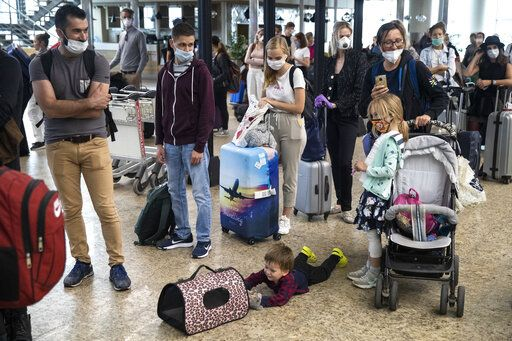 A child plays with a pet as people wait in line to check-in at Sheremetyevo international airport, outside Moscow, Russia, Saturday, Aug. 1, 2020. Russia restarts international flights to Britain, Turkey and Tanzania on Aug. 1 more than four months after closing its borders due to the coronavirus pandemic.
