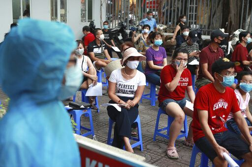 People wait in line for COVID-19 test in Hanoi, Vietnam, Friday, July 31, 2020. Vietnam reported on Friday the country's first ever death of a person with the coronavirus as it struggles with a renewed outbreak after 99 days without any cases.