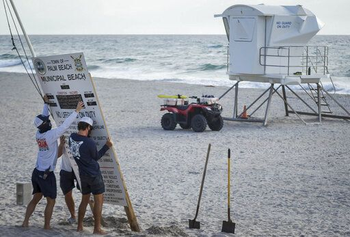 Palm Beach Ocean Rescue personnel take down the weather conditions signage in preparation for Hurricane Isaias in Palm Beach, Fla., on Saturday, Aug. 1, 2020. Forecasters are indicating there may be hurricane force winds in the county on Sunday. (Thomas Cordy/The Palm Beach Post via AP)