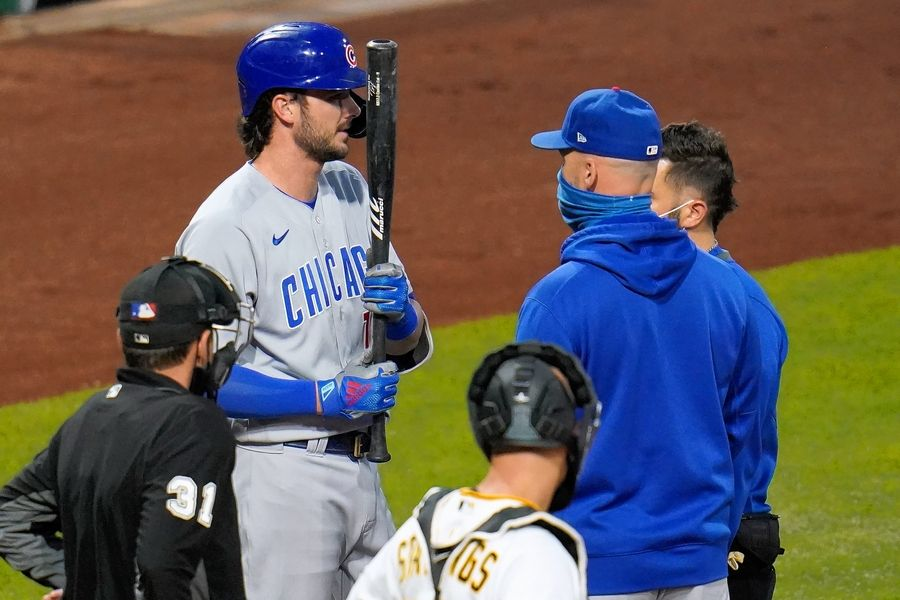 Chicago Cubs' Kris Bryant, top left, talks with manager David Ross, front right, and a team trainer during an at-bat during the second inning of a baseball game against the Pittsburgh Pirates in Pittsburgh, Monday, Sept. 21, 2020. Bryant left the game after grounding out.