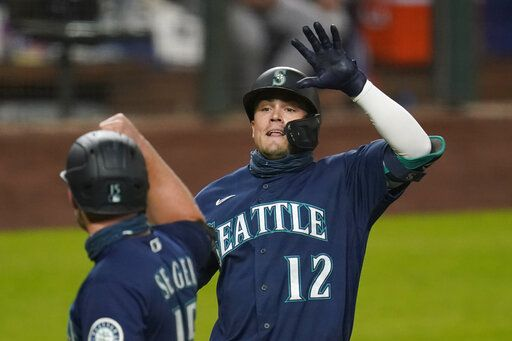 Seattle Mariners' Evan White (12) is congratulated by Kyle Seager after hitting a three-run home run against the Houston Astros in the seventh inning of a baseball game Monday, Sept. 21, 2020, in Seattle.
