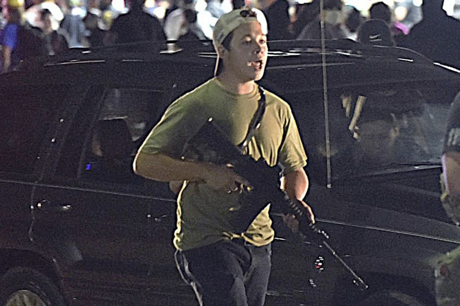 Kyle Rittenhouse carries a weapon as he walks along Sheridan Road in Kenosha, Wisconsin, during a night of unrest following the weekend police shooting of Jacob Blake. The way his lawyers tell it, the teenager wasn't a scared, gun enthusiast in over his head when he fatally shot two protesters. He was a courageous defender of liberty, a patriot exercising his right to bear arms amid chaos in the streets. But some legal experts say Rittenhouse's lawyers are taking big risks by turning a fairly straightforward self-defense case into a sweeping political argument that mirrors the law-and-order reelection campaign of President Donald Trump.