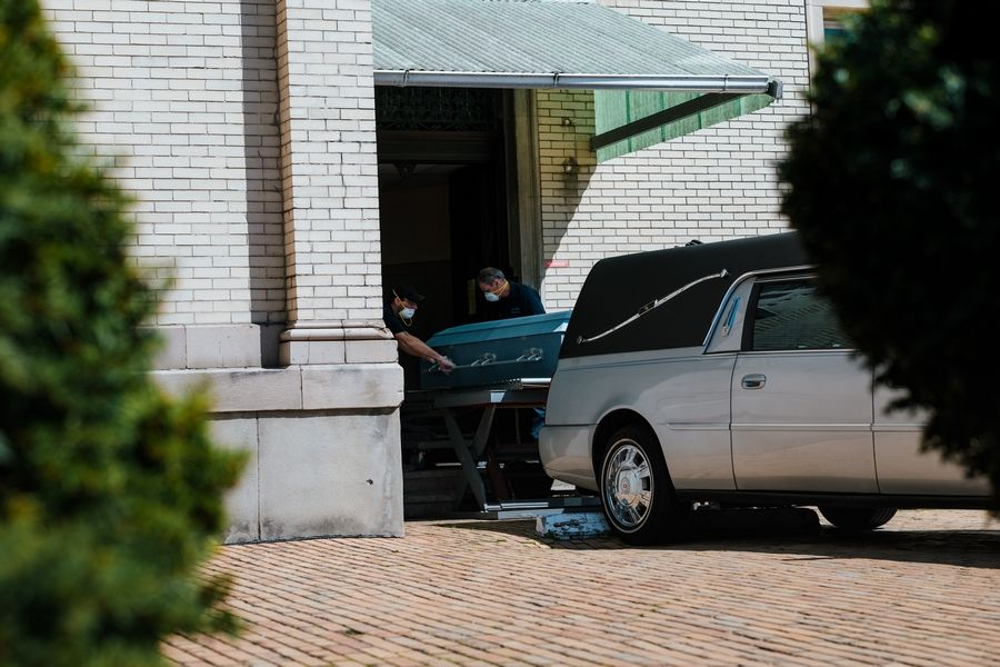 Workers at Fresh Pond Crematory in Queens, N.Y., receive a casket. The vast number of deaths in April during the coronavirus outbreak compelled a local funeral home to insist upon cremation for all services.