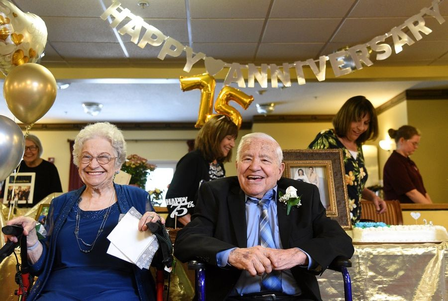 Last year, Carmen and Mary Siciliano celebrate their 75th wedding anniversary at Heritage Woods in Batavia. Behind them, their daughters, Gayle Siciliano Grazian, center, and Joyce Siciliano Andringa prepare the cake.