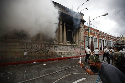 Clouds of smoke shoot out from the Congress building after protesters set a part of it on fire, in Guatemala City, Saturday, Nov. 21, 2020. Hundreds of protesters were protesting in various parts of the country Saturday against Guatemalan President Alejandro Giammattei and members of Congress for the approval of the 2021 budget that reduced funds for education, health and the fight for human rights.