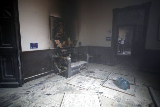 A couch and art work destroyed by fire are seen inside the Congress building after protesters set a part of the building on fire, in Guatemala City, Saturday, Nov. 21, 2020. Hundreds of protesters were protesting in various parts of the country Saturday against Guatemalan President Alejandro Giammattei and members of Congress for the approval of the 2021 budget that reduced funds for education, health and the fight for human rights.