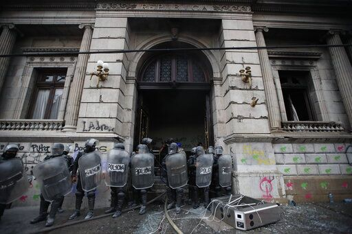 Police surround the Congress building after protesters set a part of it on fire, in Guatemala City, Saturday, Nov. 21, 2020. Hundreds of protesters were protesting in various parts of the country Saturday against Guatemalan President Alejandro Giammattei and members of Congress for the approval of the 2021 budget that reduced funds for education, health and the fight for human rights.