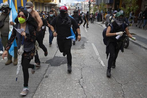 Protestors take chase from advancing police after protesters set a part of the Congress building on fire, in Guatemala City, Saturday, Nov. 21, 2020. Hundreds of protesters were protesting in various parts of the country Saturday against Guatemalan President Alejandro Giammattei and members of Congress for the approval of the 2021 budget that reduced funds for education, health and the fight for human rights.