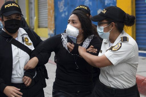 A woman is detained by police near the Congress building after protesters set a part of the building on fire, in Guatemala City, Saturday, Nov. 21, 2020. Hundreds of protesters were protesting in various parts of the country Saturday against Guatemalan President Alejandro Giammattei and members of Congress for the approval of the 2021 budget that reduced funds for education, health and the fight for human rights.
