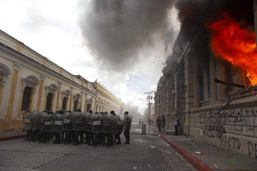 Flames shoot out from the Congress building after protesters set a part of the building on fire, in Guatemala City, Saturday, Nov. 21, 2020. Hundreds of protesters were protesting in various parts of the country Saturday against Guatemalan President Alejandro Giammattei and members of Congress for the approval of the 2021 budget that reduced funds for education, health and the fight for human rights.