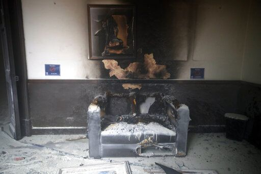 A couch and art work destroyed by fire are seen inside the Congress building after protesters set a part of building on fire, in Guatemala City, Saturday, Nov. 21, 2020. Hundreds of protesters were protesting in various parts of the country Saturday against Guatemalan President Alejandro Giammattei and members of Congress for the approval of the 2021 budget that reduced funds for education, health and the fight for human rights.