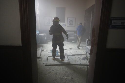 A firefighter walks inside the Congress building after protesters set a part of the building on fire, in Guatemala City, Saturday, Nov. 21, 2020. Hundreds of protesters were protesting in various parts of the country Saturday against Guatemalan President Alejandro Giammattei and members of Congress for the approval of the 2021 budget that reduced funds for education, health and the fight for human rights.
