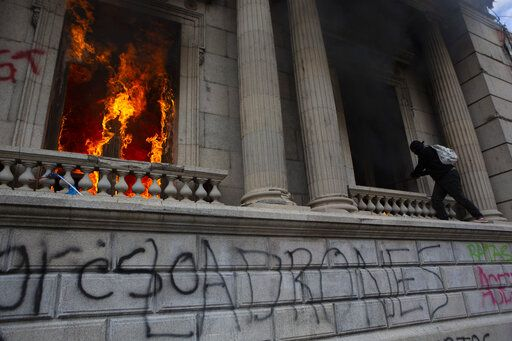 Flames shoot out from a corridor of the Congress building after protesters set a part of the building on fire, in Guatemala City, Saturday, Nov. 21, 2020. Hundreds of protesters were protesting in various parts of the country Saturday against Guatemalan President Alejandro Giammattei and members of Congress for the approval of the 2021 budget that reduced funds for education, health and the fight for human rights.