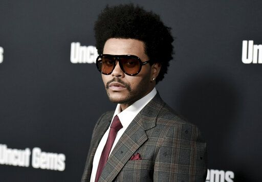 "FILE - The Weeknd attends the LA premiere of ""Uncut Gems"" at ArcLight Hollywood on Wednesday, Dec. 11, 2019, in Los Angeles. The Weeknd angrily slammed the Grammys, calling the collective 'œcorrupt'� after the pop star received zero nominations despite having multiple hits this year. The three-time Grammy winner criticized the Recording Academy on Tuesday after he was severely snubbed after having one of the year's biggest albums with 'œAfter Hours'� and being tapped as the Super Bowl halftime headline performer. (Photo by Richard Shotwell/Invision/AP, File)"