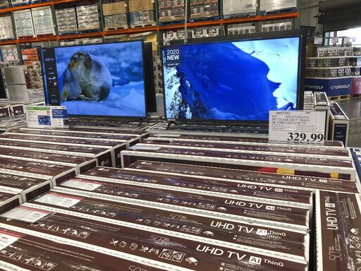 Rows of boxed big-screen televisions sit on display at a Costco warehouse in this photograph taken Wednesday, Nov. 18, 2020, in Sheridan, Colo.   Orders for big-ticket manufactured goods slow to modest gain of 1.3% in October indicating economy is slowing.