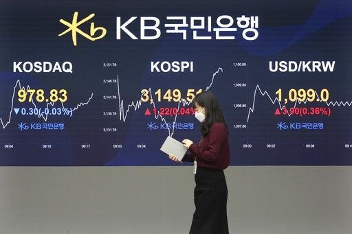 A currency trader passes by monitors showing the Korea Composite Stock Price Inde, and foreign exchange rate at the foreign exchange dealing room of a KB Kookmin Bank branch in Seoul, South Korea, Thursday, Jan. 14, 2021. Shares were mostly higher in Asia on Thursday after a lackluster day on Wall Street, where major indexes spent the day drifting up and down near their record highs.