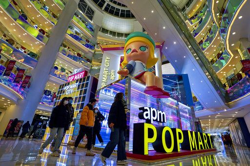 Shoppers wearing face masks to help curb the spread of the coronavirus wall by the Chinese toy maker POP Mart display booth at a shopping mall in Beijing on Dec. 9, 2020. China's economy grew 2.3% in 2020 as a recovery from the coronavirus pandemic accelerated while the United States, Europe and Japan struggled with disease flare-ups.
