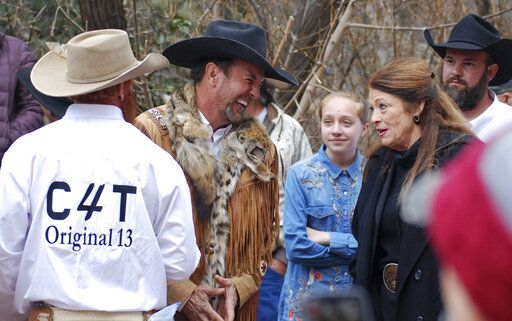 "FILE - In this March 12, 2019, file photo, Cowboys for Trump leader and Otero County Commissioner Couy Griffin, center, talks with Republican New Mexico state Rep. Candy Ezzell of Roswell, N.M., at a protest against gun control and pro-abortion rights legislation outside the New Mexico State Capitol, in Santa Fe, N.M. A New Mexico county official who runs a group called ""Cowboys for Trump"" who had vowed to return to Washington after last week's riot at the U.S. Capitol to place a flag on House Speaker Nancy Pelosi's desk was arrested by the FBI on Sunday, Jan. 17, 2021. Griffin was arrested on charges of illegally entering the U.S. Capitol."