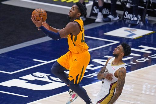 Utah Jazz guard Donovan Mitchell, left, goes to the basket as New Orleans Pelicans guard Nickeil Alexander-Walker defends during the first half of an NBA basketball game Tuesday, Jan. 19, 2021, in Salt Lake City.