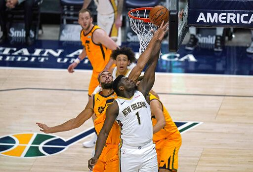 New Orleans Pelicans forward Zion Williamson (1) lays the ball up as Utah Jazz center Rudy Gobert, left, and others defend during the first half of an NBA basketball game Tuesday, Jan. 19, 2021, in Salt Lake City.
