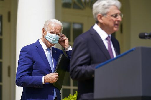 President Joe Biden, adjusts his face mask as he listens to Attorney General Merrick Garland speak about gun violence prevention in the Rose Garden at the White House, Thursday, April 8, 2021, in Washington.
