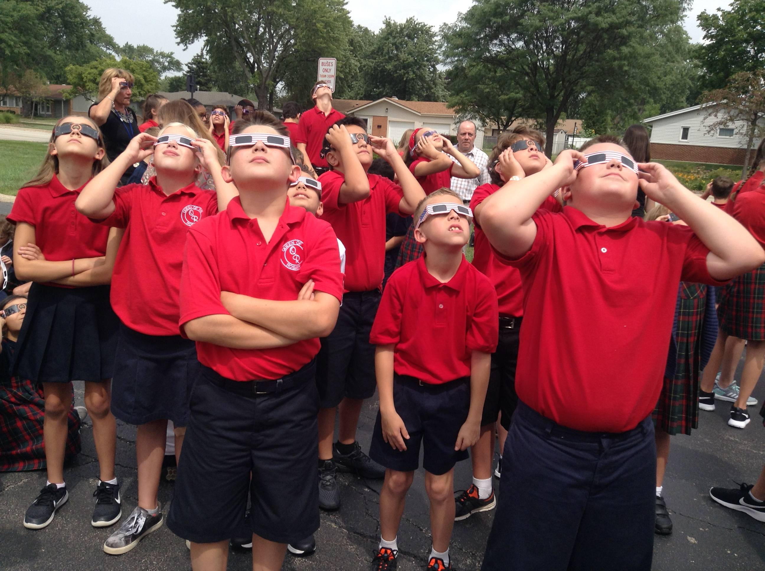 Queen of the Rosary School students view the eclipse.