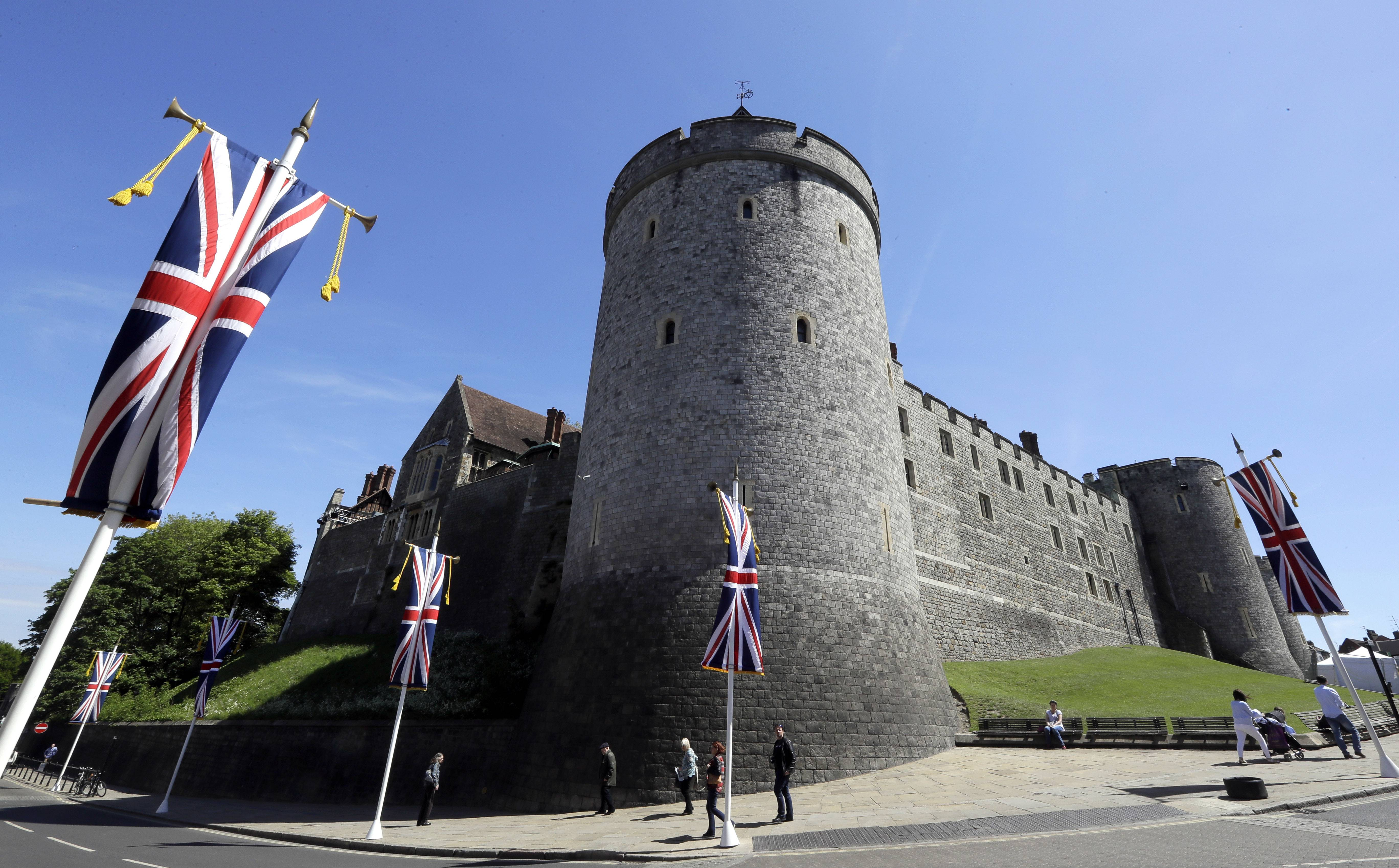 Flags fly in front of the castle in Windsor, England, Monday. Preparations are being made in the town ahead of the wedding of Britain's Prince Harry and Meghan Markle that will take place in Windsor on Saturday.