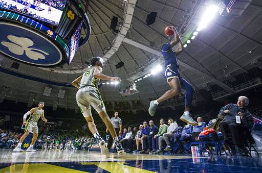 Notre Dame's D.J. Harvey (5) leaps to keep the ball in play as Chicago State's Cameron Bowles (21) watches during an NCAA college basketball game Thursday, Nov. 8, 2018, in South Bend, Ind. (Michael Caterina/South Bend Tribune via AP)