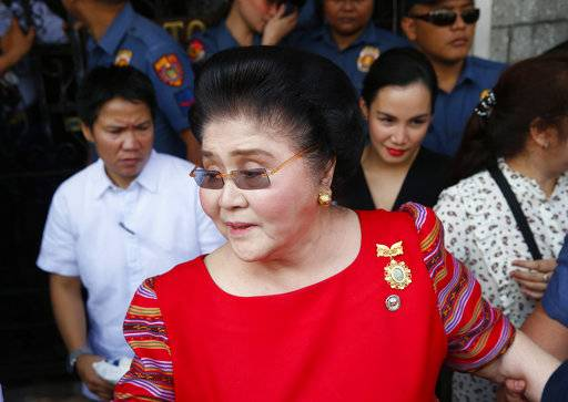 FILE - In this Oct. 16, 2018, file photo, former Philippines first lady and widow of the late dictator Ferdinand Marcos, Congresswoman Imelda Marcos arrives at the Commission on Elections to lend her support for her daughter Governor Imee Marcos in filing her Certificate of Candidacy or COC for a Senate seat in the May 2019 midterm elections in Manila, Philippines. A Philippine court found former first lady Imelda Marcos guilty of graft and ordered her arrest Friday, Nov. 9, 2018, in a rare conviction among many corruption cases that she's likely to appeal to avoid jail and losing her seat in Congress.